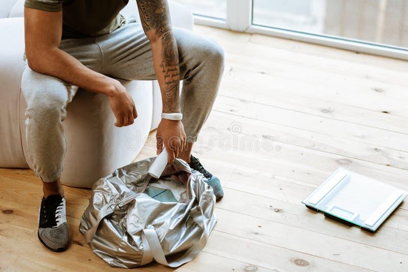 Desportista com a tatuagem disponível que embala seu saco para o gym fotos de stock royalty free