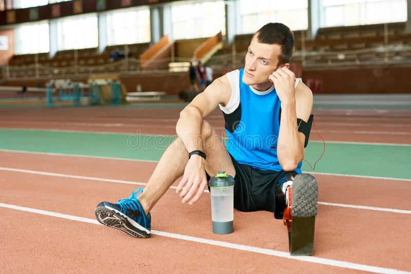 Desportista do amputado que descansa na pista de atletismo imagens de stock