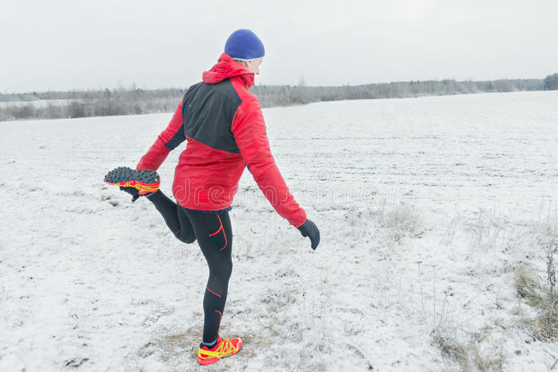 Desportista durante a sessão de formação do inverno no fundo nevado do campo fora imagem de stock