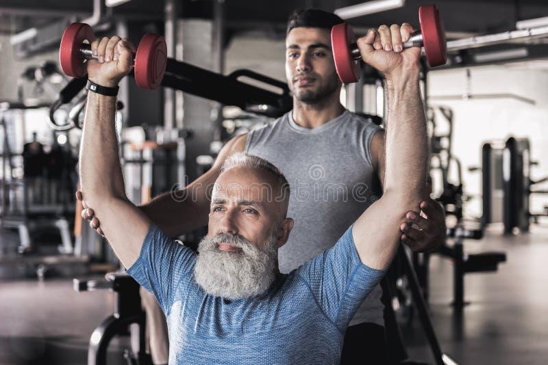 Desportista idoso sério que faz exercícios no gym moderno com instrutor imagens de stock