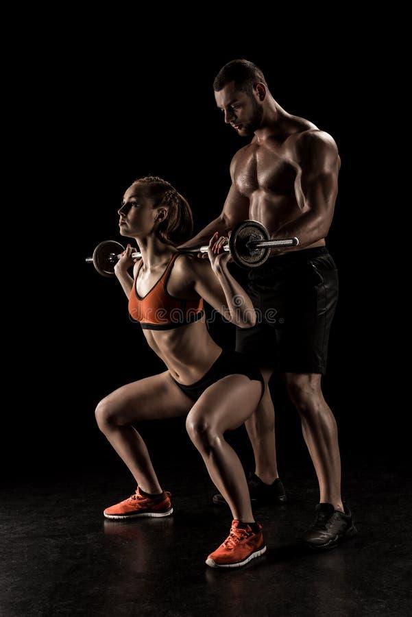 Desportista muscular que ajuda o barbell de levantamento da jovem mulher desportiva imagens de stock