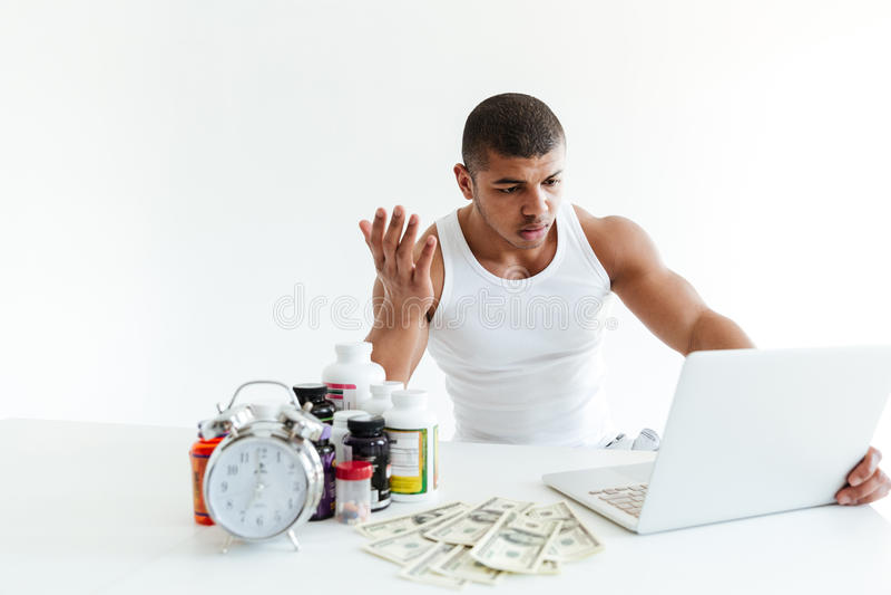 Desportista novo confuso perto do dinheiro e nutrição do esporte usando o portátil fotos de stock royalty free