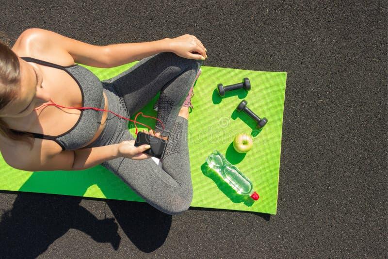 Desportista novo da aptidão que senta e que usa o smartphone no gym Menina na esteira da ioga com botte da água, do peso e da maç fotos de stock