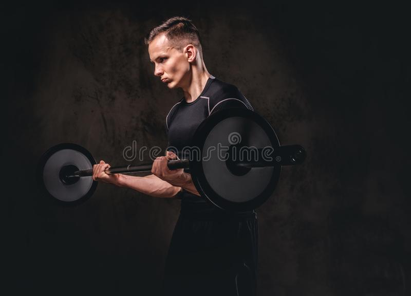Desportista novo focalizado que guarda um barbell e que faz o exercício no bíceps Isolado no fundo escuro foto de stock royalty free