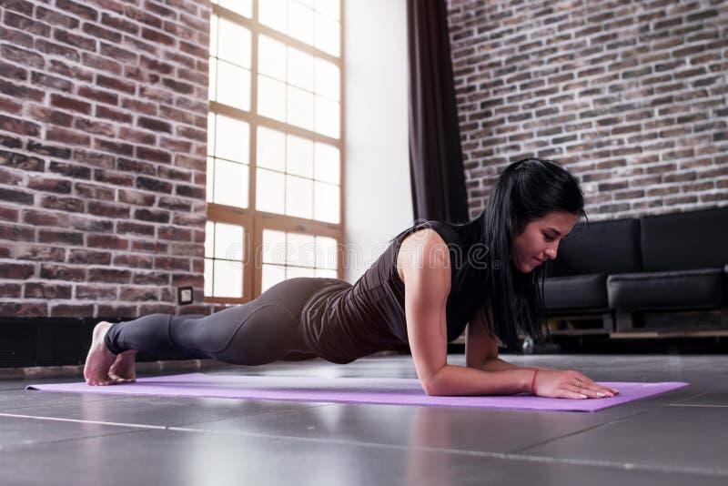 Desportista novo que dá certo em casa fazendo o exercício da prancha na esteira da ioga fotos de stock