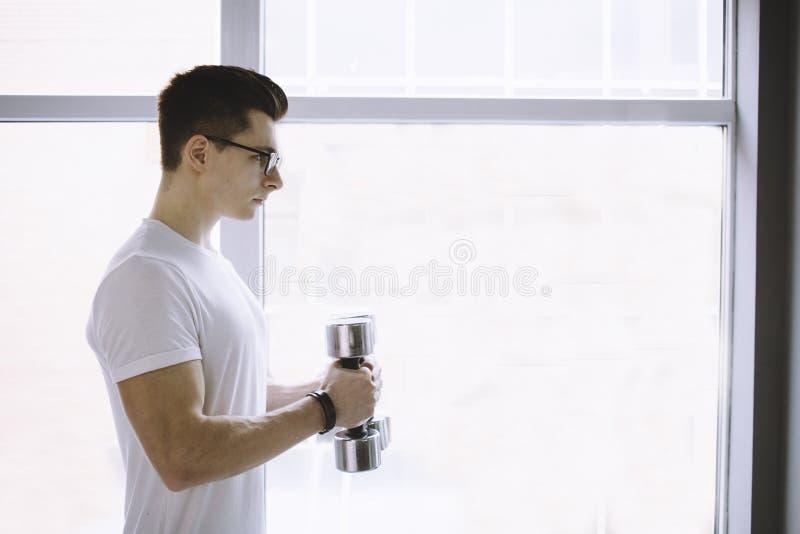 Desportista novo que faz o exercício com peso foto de stock