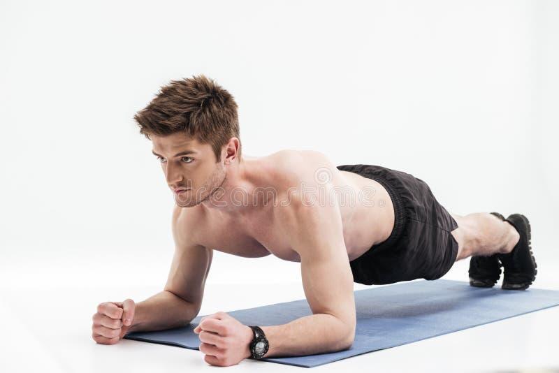 Desportista novo que faz o exercício da prancha em uma esteira da aptidão fotografia de stock