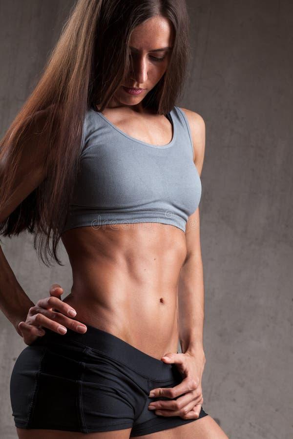 Desportista novo que mostra o músculo do Abs imagens de stock royalty free