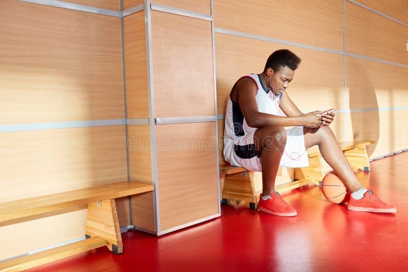 Desportista preto que usa o smartphone e escutando a música foto de stock