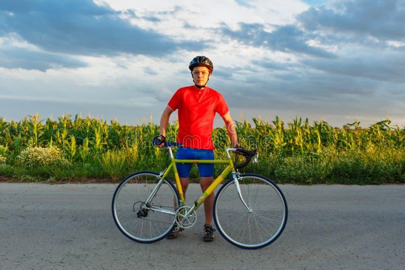 Desportista que está ao lado da bicicleta Engrenagem, capacete e vidros vestindo dos esportes Fundo natural Céu bonito, azul fotografia de stock