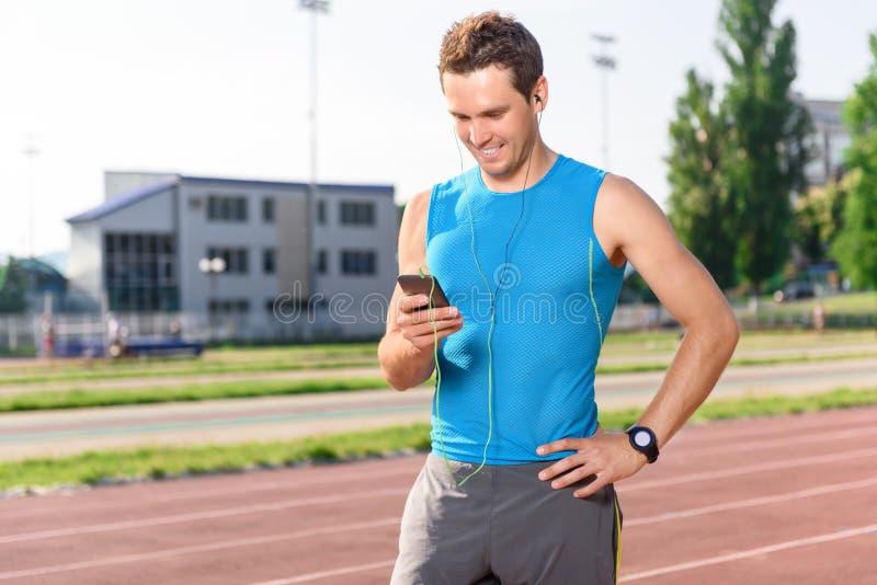 Desportista que está com telefone celular no estádio imagens de stock royalty free