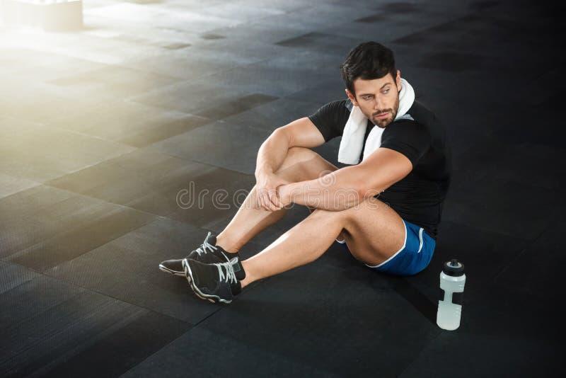 Desportista que senta-se no assoalho no gym imagem de stock royalty free