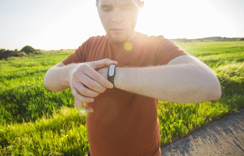 Desportista que verifica seu pulso no perseguidor esperto do relógio fotos de stock