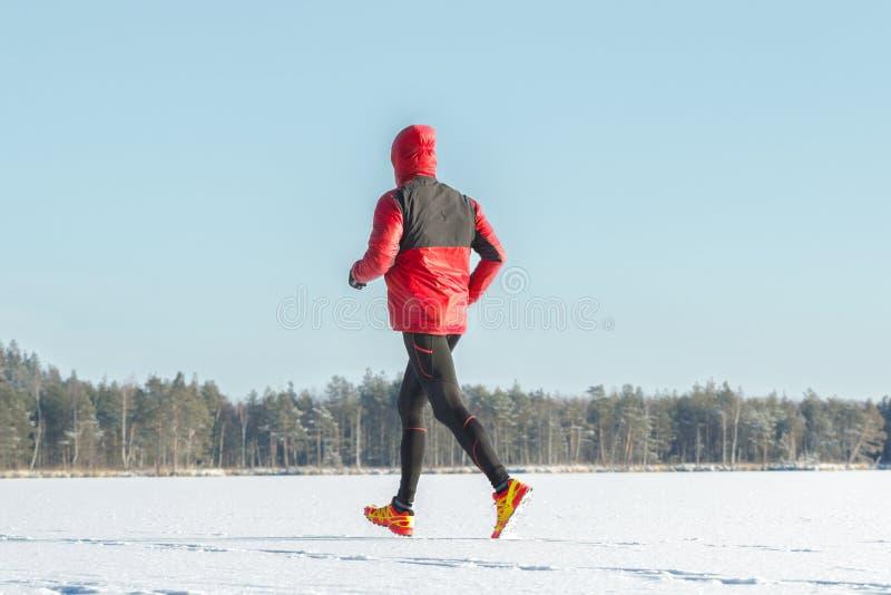 Desportista running no sportswear protetor que faz a sessão de formação do inverno fora fotografia de stock royalty free