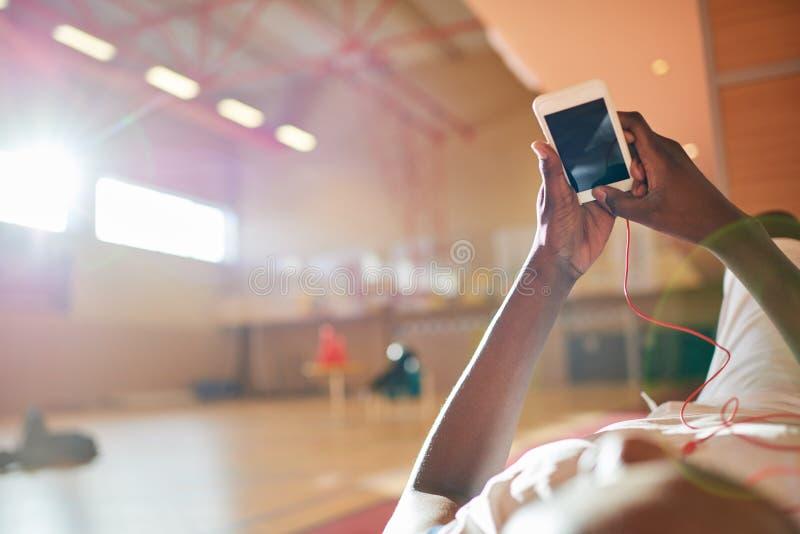 Desportista sem cara que usa o smartphone imagens de stock