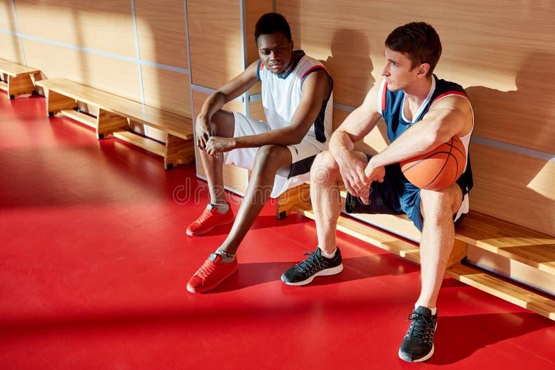 Desportistas no banco no gym imagem de stock royalty free