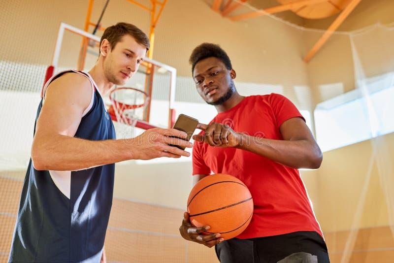 Desportistas que usam o smartphone no campo de básquete imagens de stock