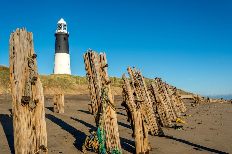Desprecie el faro del punto y las viejas defensas de mar de madera de la playa fotos de archivo libres de regalías