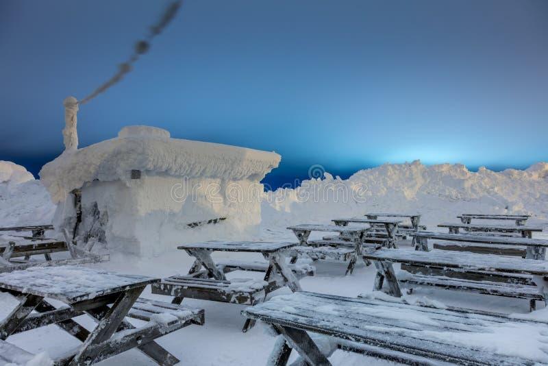 Después de ventisca - la pequeña casa de madera cubrió nieve grande imagen de archivo