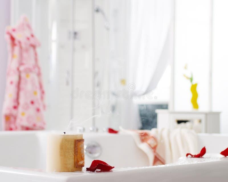 Después del baño - cierre para arriba del interior del cuarto de baño con el foco corto en el pétalo color de rosa y la vela que  fotos de archivo