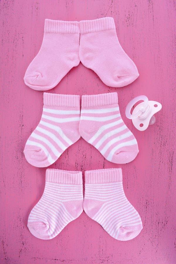 Dess uppvaktar ett flickababy shower- eller barnkammarebegrepp med sockor på rosa färger arkivbild