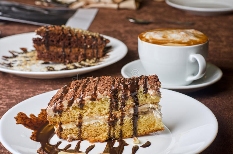 Dessert. Cakes with banana and coffee at table stock images