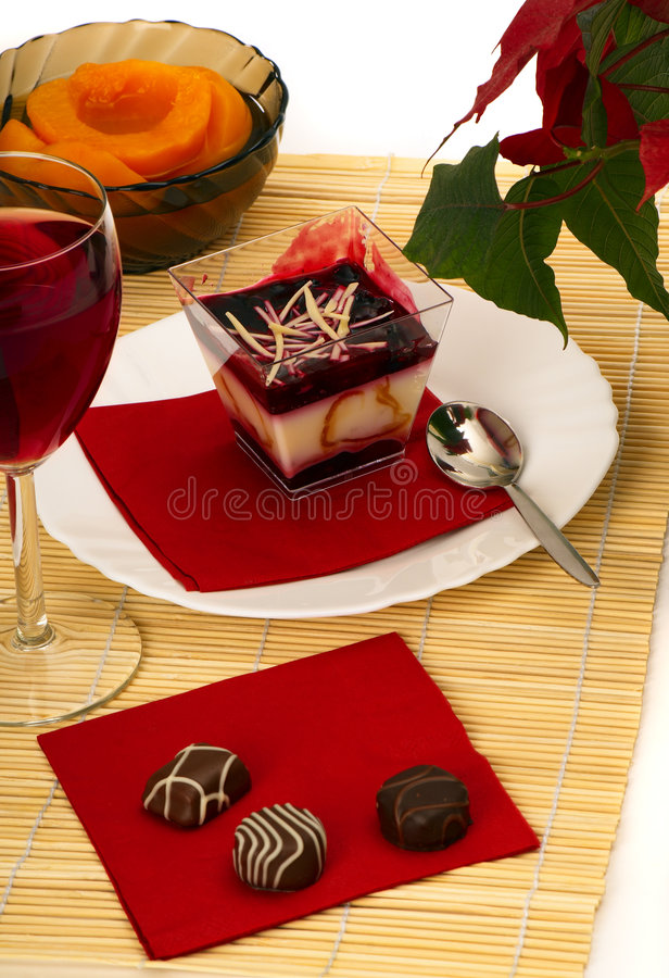 Dessert. Still-life with a dessert, chocolates, red wine and peaches royalty free stock photo