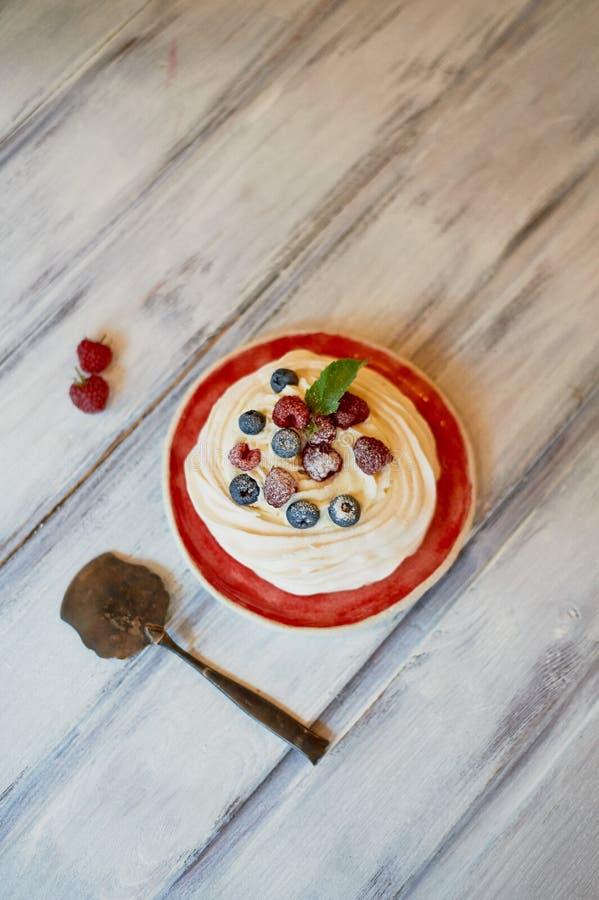 Dessert Anna Pavlova met frambozen en bosbessen op witte houten oppervlakte royalty-vrije stock afbeelding