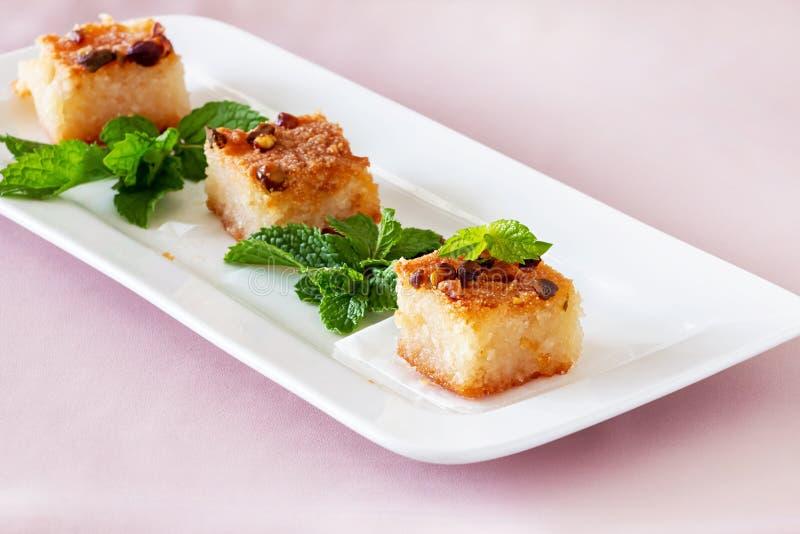 Dessert arabe traditionnel de Basbousa ou de Namoora Gâteau fait maison délicieux de semoule avec des écrous du plat blanc photo libre de droits