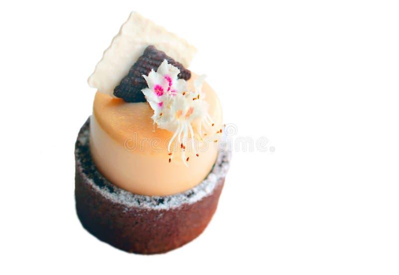 Dessert arancio della molla del mango con il confine della spugna del cioccolato ed i fiori freschi della castagna isolati su fon immagini stock