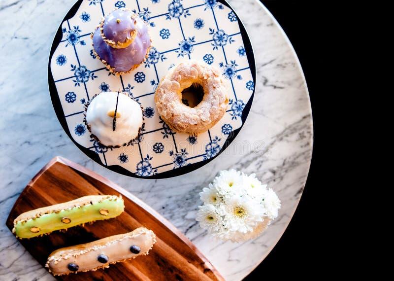 Dessert assorti sur la table mable blanche, beignet, gâteau de tasse, eclaire photo libre de droits