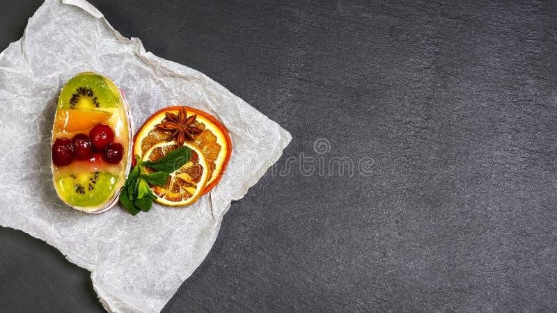 Dessert au goût âpre de fruit frais et de baie avec du sucre de lancer Gâteau doux délicieux avec le kiwi, l'orange et la cerise  image libre de droits