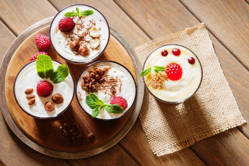 Dessert avec les baies, la gelée, la crème, les écrous et la feuille en bon état sur un conseil en bois de coupe photos libres de droits