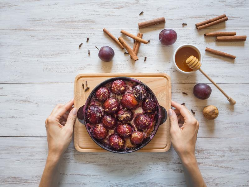 Dessert of baked plum in a pan with cloves, cinnamon, honey and zest. Dessert of baked plum in a pan with cloves, cinnamon, honey and zest royalty free stock photo