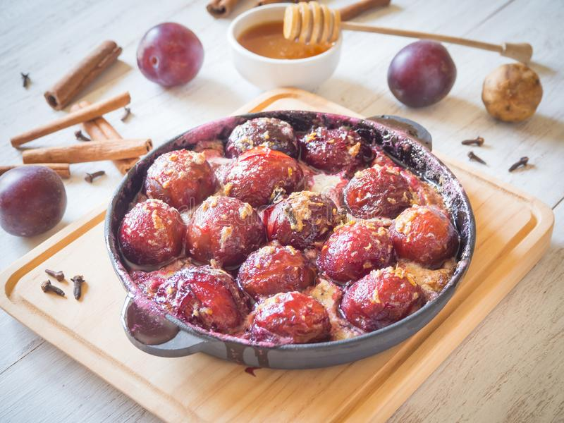 Dessert of baked plum in a pan with cloves, cinnamon, honey and zest. Dessert of baked plum in a pan with cloves, cinnamon, honey and zest royalty free stock photography