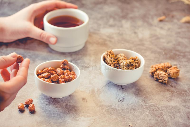 Dessert bars made of sunflower seeds  in a honey caramel. Gozinak, Caramelized peanuts in white bowl and on gray background..The. Process of eating. In the stock image