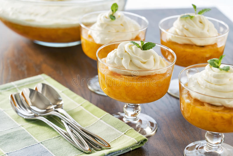 Dessert bowls are full of Jell-o and a creamy whipped topping stock image