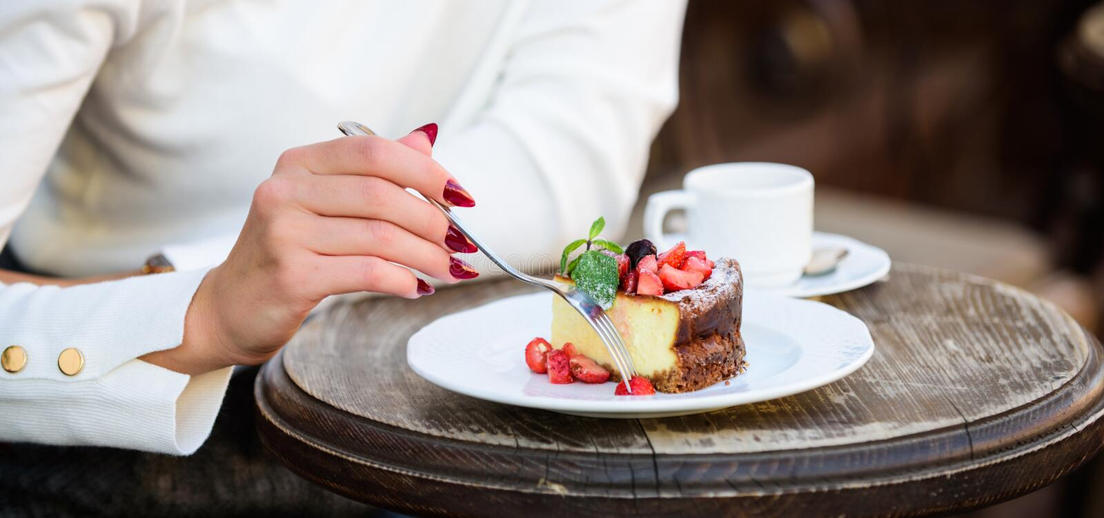 Dessert cake cup of coffee and female hand with fork close up. Piece of cake with red berry. Gourmet recipe food. Cake. Slice on white plate. Cake with cream royalty free stock photos