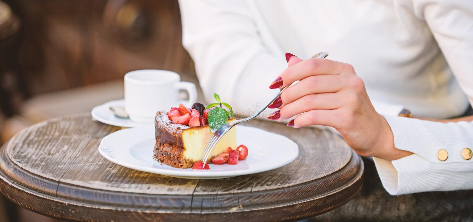 Dessert cake cup of coffee and female hand with fork close up. Piece of cake with red berry. Gourmet recipe food. Cake. Slice on white plate. Cake with cream stock images
