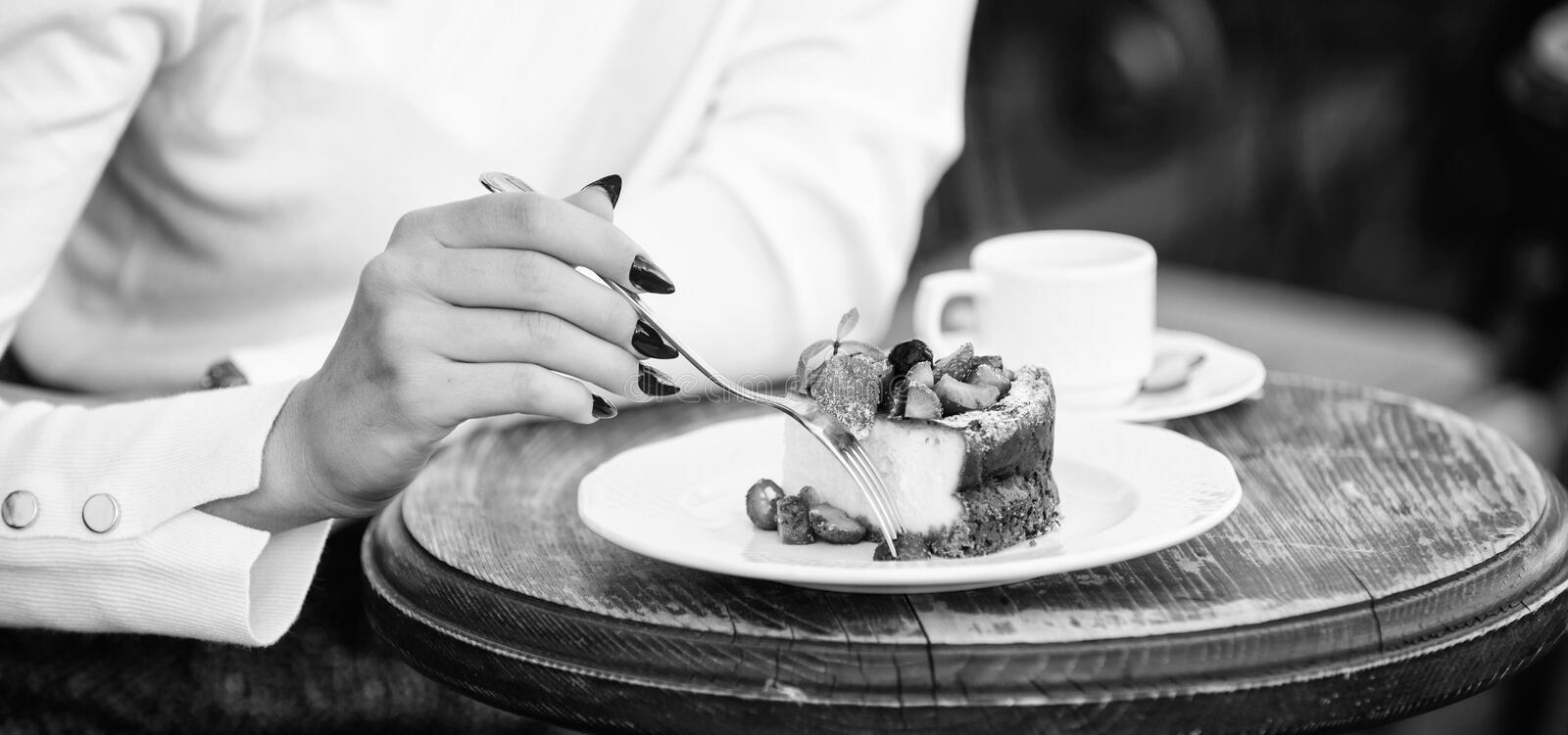 Dessert cake cup of coffee and female hand with fork close up. Piece of cake with red berry. Gourmet recipe food. Cake. Slice on white plate. Cake with cream royalty free stock photo