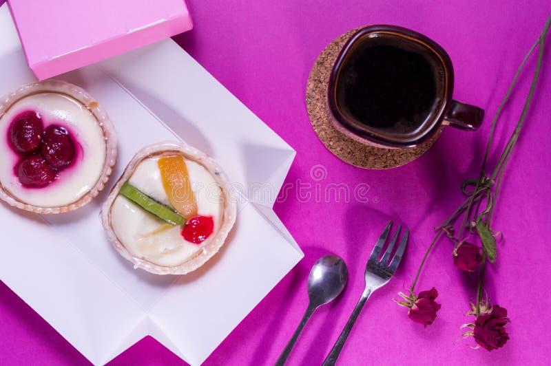 Dessert cakes with cream and fruit. Bright background. Pink setting. Dessert cakes with cream and fruit. Bright background. Pink room. Top stock photography