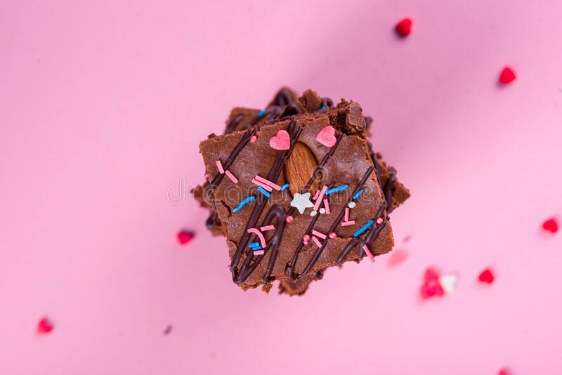 Dessert chocolate brownie with walnut almonds, on a pink background. Delicious and sweet desserts. Cake stock photo