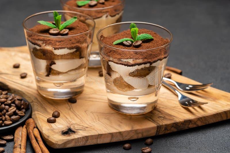 Dessert classico di tiramisù con cioccolato in un boartd tagliente non di legno di vetro su fondo concreto scuro immagini stock