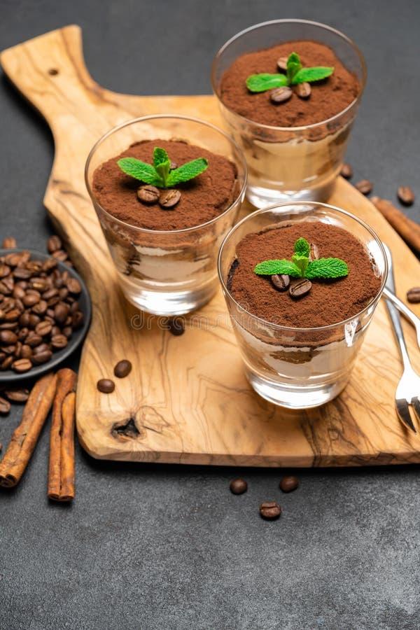 Dessert classico di tiramisù con cioccolato in un boartd tagliente non di legno di vetro su fondo concreto scuro immagine stock libera da diritti