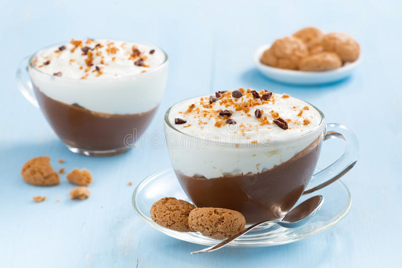 Dessert con cioccolato, crema e il amaretti su una tavola blu immagine stock