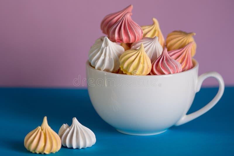 Dessert con meringa, molte meringhe variopinte nella tazza di tè immagini stock