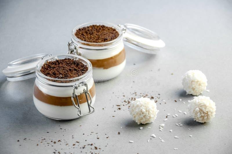 Dessert crémeux de mousse de vanille et de chocolat dans le pot avec des boules de noix de coco sur Gray Background jour du ` s d photographie stock libre de droits