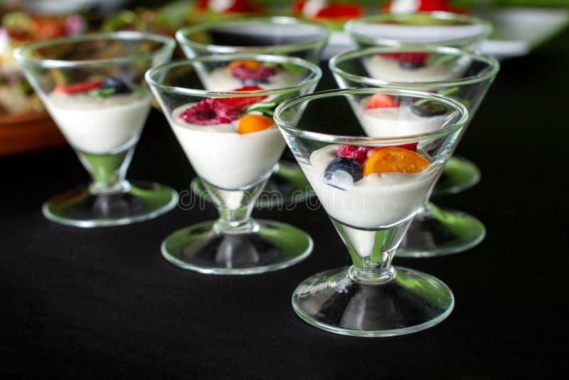 Dessert cremoso con le bacche di estate in una ciotola di vetro del gelato fotografie stock