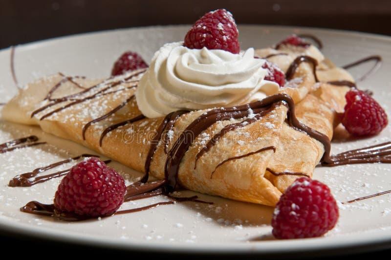 Dessert crepe with fresh raspberries. Whipped cream and chocolate stock photos