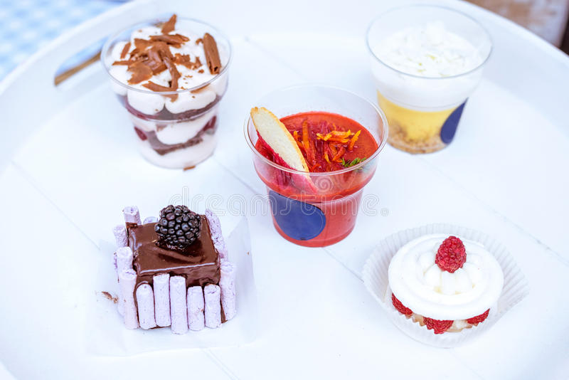 Dessert in cups and white plate royalty free stock images